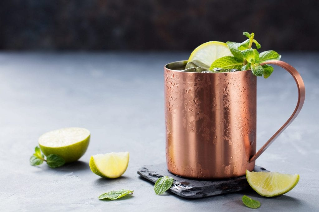 Cold Moscow Mules cocktail with ginger beer, vodka, lime Grey stone background.